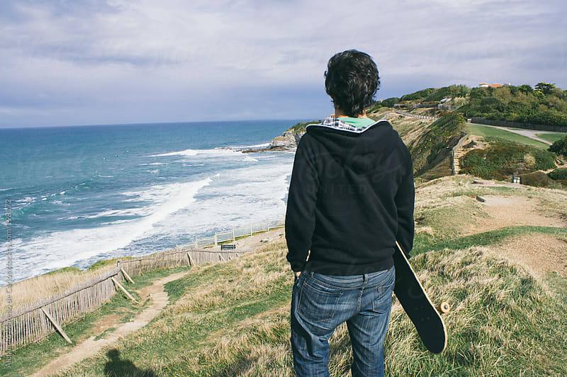 Young man with a skateboard on the coast promenade by Alejandro Moreno de Carlos for Stocksy United