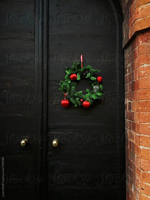 Christmas pine branches wreath hanging on old wooden main door in italian street by Laura Stolfi for Stocksy United