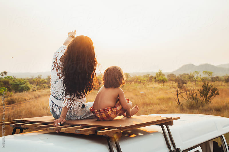 On The Road - Pretty Brunette Sitting With 3-Year Old Sun on Camper Van Roof and Watching Sunset by VISUALSPECTRUM for Stocksy United