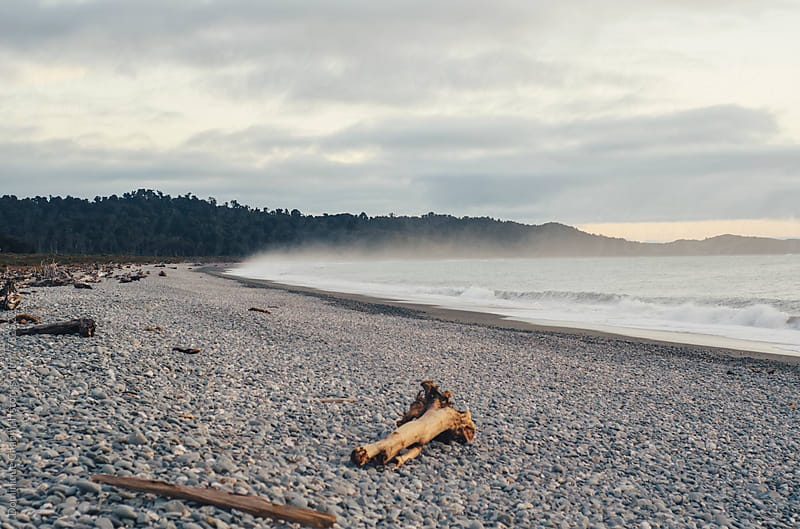 Mist covered pebble beach by Dominique Chapman for Stocksy United