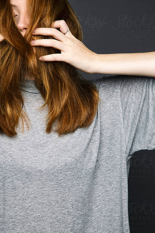 Young redheaded woman hiding her face behind her hair by Danil Nevsky for Stocksy United