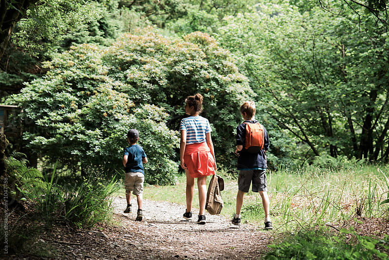 three kids walking on a path by Léa Jones for Stocksy United