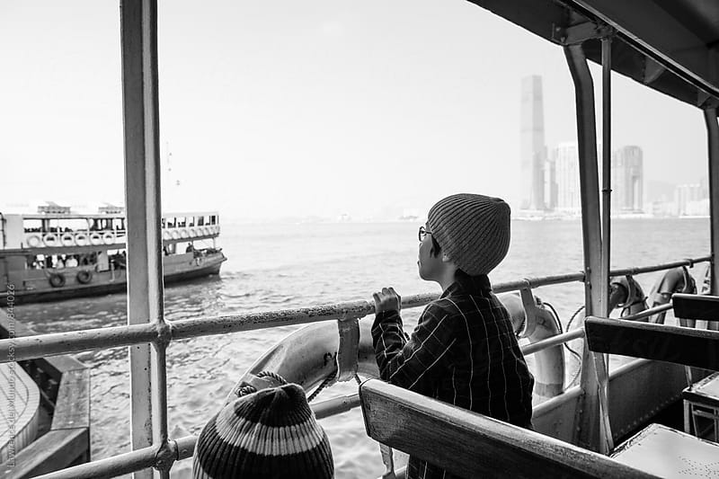 A young boy looking out into the bay  and watching other boats pass while on a ferry boat ride. by Lawrence del Mundo for Stocksy United