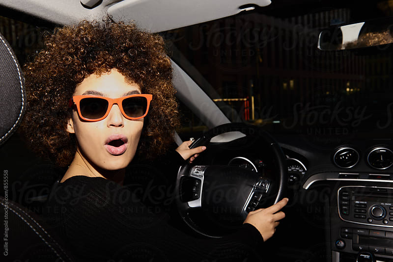 Afro young woman in sunglasses driving a car by Guille Faingold for Stocksy United