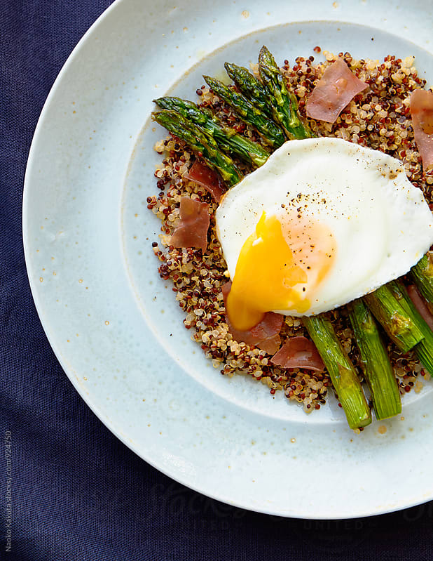 sunny side up with roasted asparagus, prosciutto over quinoa on light blue plate by Naoko Kakuta for Stocksy United