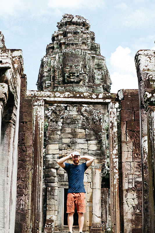 Young male stands in front of temple on adventure by Jesse Morrow for Stocksy United