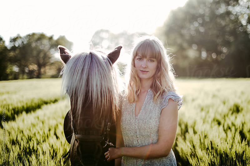A girl with her horse standing in a corn field by Christian Zielecki for Stocksy United