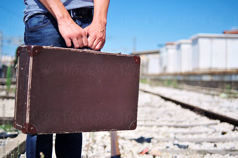 young man with a suitcase on the railroad by juan moyano for Stocksy United
