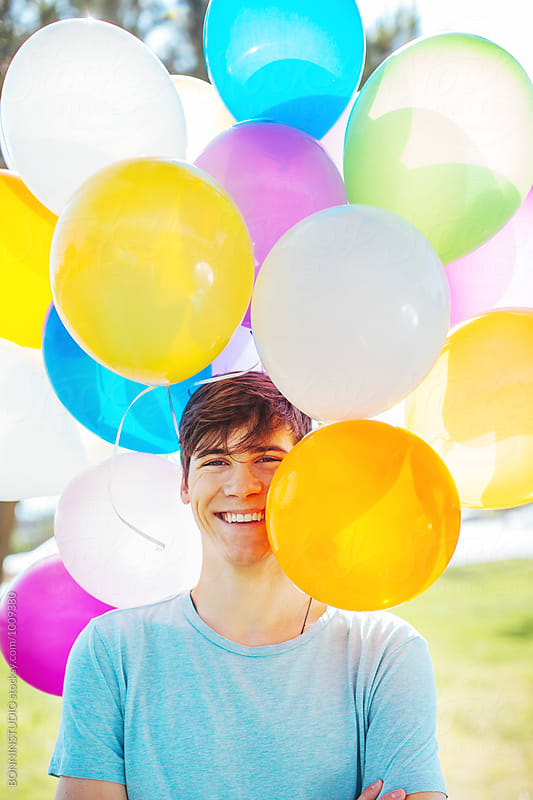 Portrait of a young boy smiling between colorful balloons.  by BONNINSTUDIO for Stocksy United