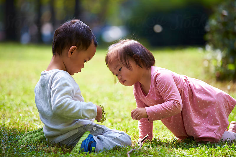 two lovely kids together on the lawn by cuiyan Liu for Stocksy United