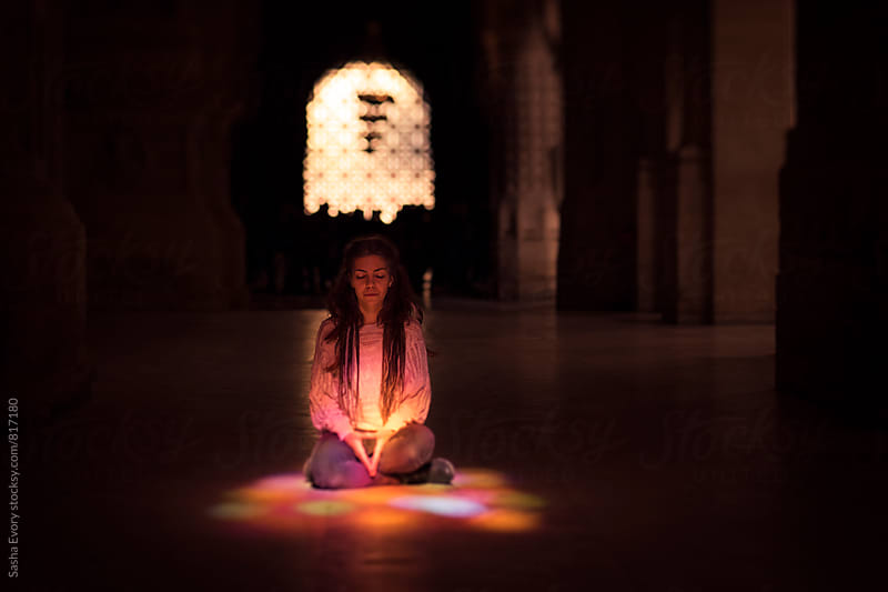A girl meditating inside the temple by Sasha Evory for Stocksy United