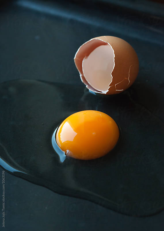 Fresh raw egg on a dark background by Jelena Jojic Tomic for Stocksy United