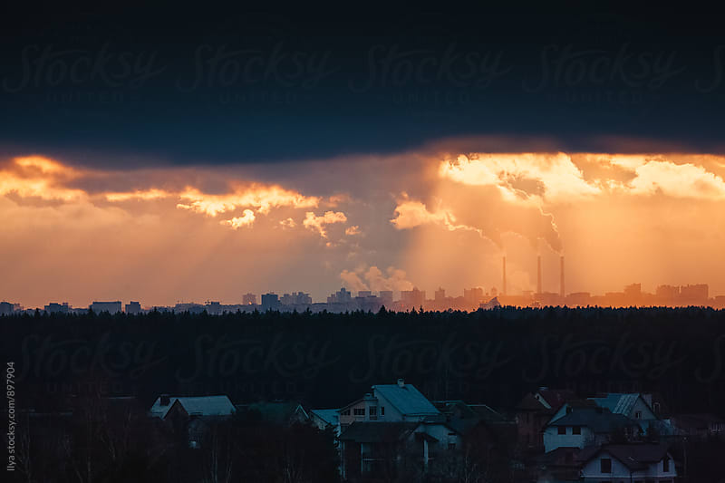 Smoke raising from factory chimneys above the city by Ilya for Stocksy United