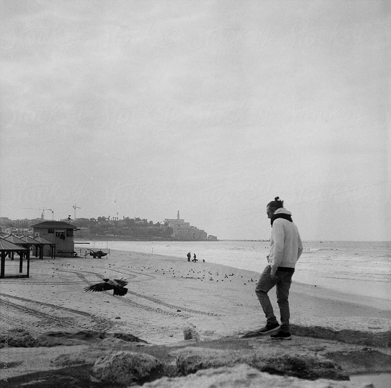 A black and white film photo of man frightening a bird in front of sea by Anna Malgina for Stocksy United
