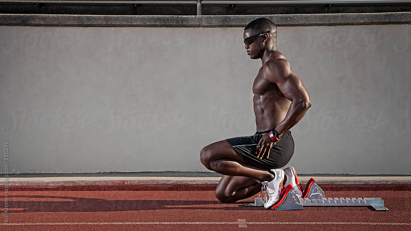 African American male sprinter on the blocks by Neil Kremer for Stocksy United