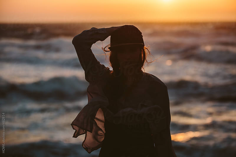 The silhouette of a young woman on the California coast at sunset  by HOWL for Stocksy United