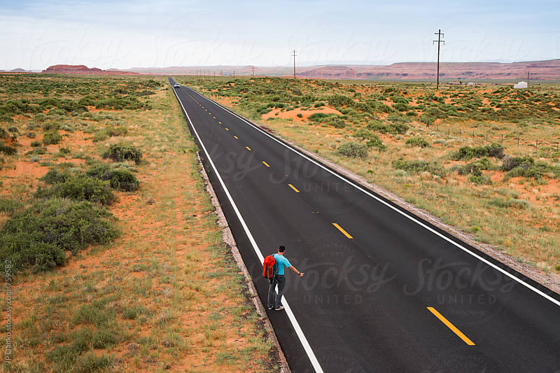 Male Hitchhiker Thumbing for A Ride on A Remote Highway Extending to Horizon in Arizona by JP Danko for Stocksy United
