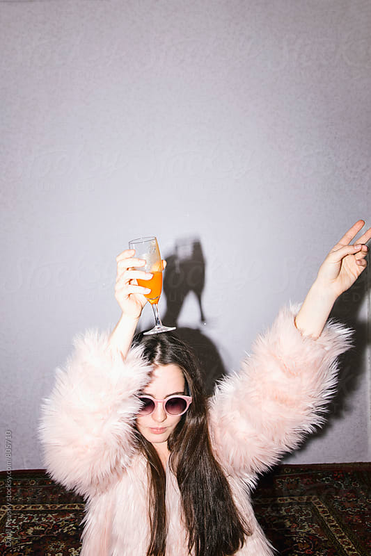 Young woman in pink faux fur coat holding glass of orange juice by Danil Nevsky for Stocksy United
