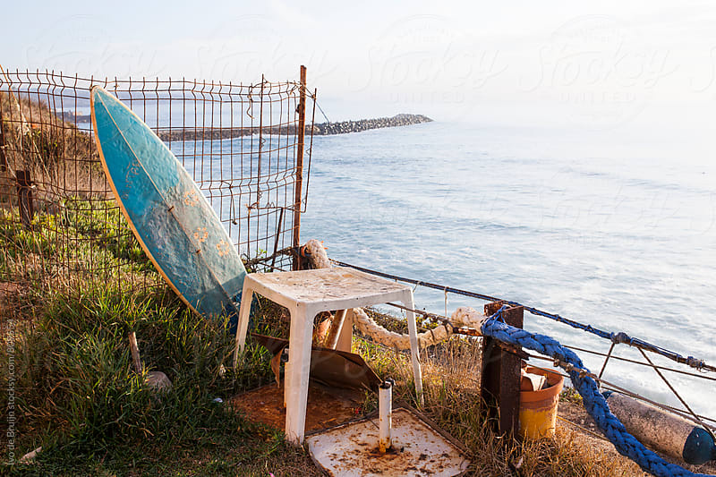 Old school surfboard and other stuff standing on a cliff,  with the Atlantic Ocean in the background by Ivo de Bruijn for Stocksy United