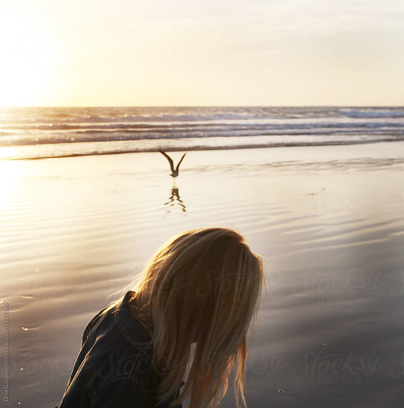 Girl standing by ocean looking down with one bird hovering over head by Dina Giangregorio for Stocksy United