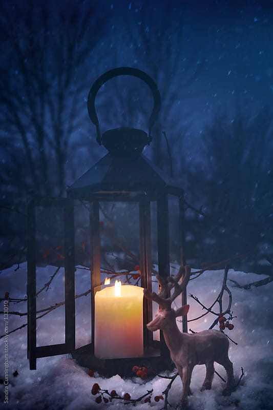 Lit lantern in the snow on a snowy night by Sandra Cunningham for Stocksy United