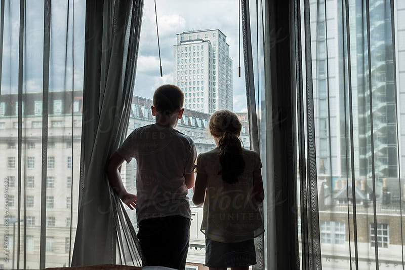 Two children looking out of a window. by Craig Holmes for Stocksy United