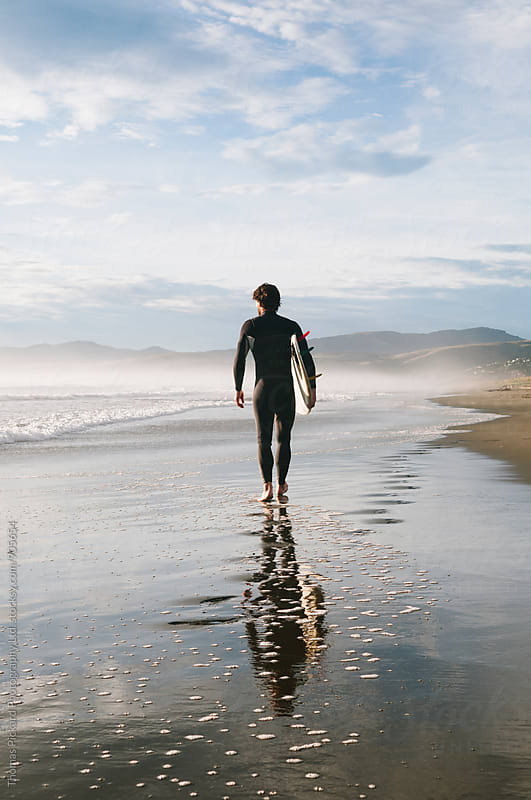 Surfer walking along beach with surfboard in early morning light, New Zealand. by Thomas Pickard for Stocksy United