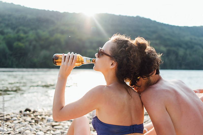 Friends drinking beer on the river bank by Boris Jovanovic for Stocksy United