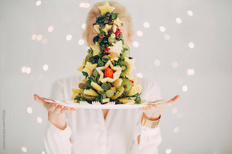 Woman Holding a Christmas Tree Made of Fruit by Lumina for Stocksy United