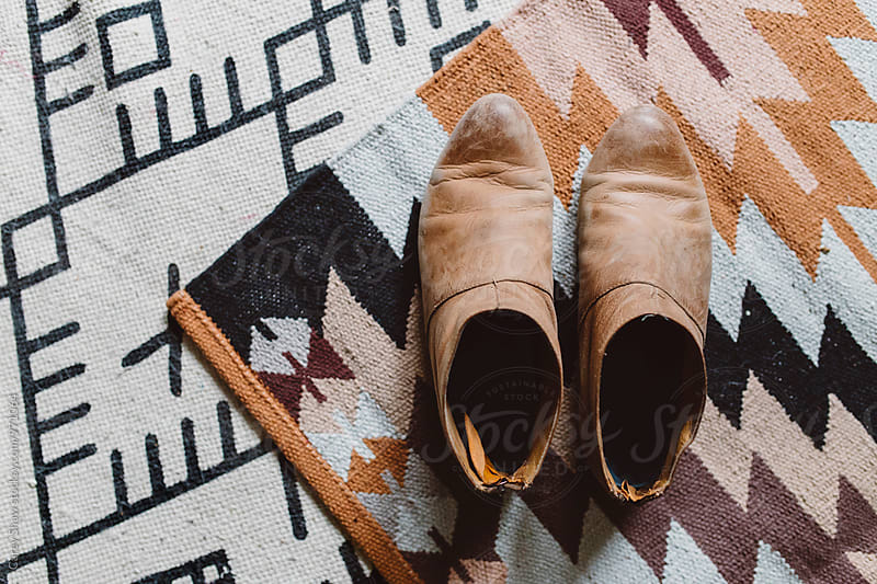 Worn leather booties on patterned rugs by Carey Shaw for Stocksy United