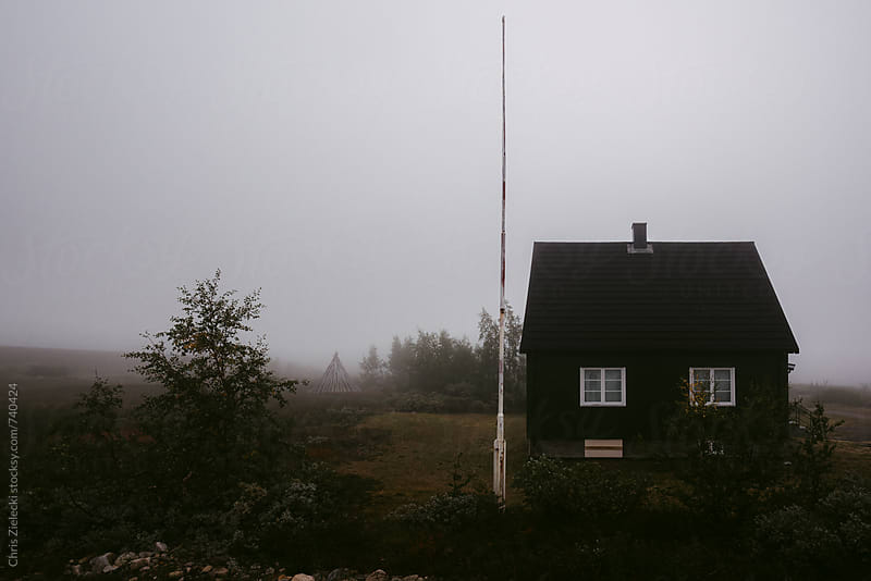 a lonely wooden house in the fog by Christian Zielecki for Stocksy United