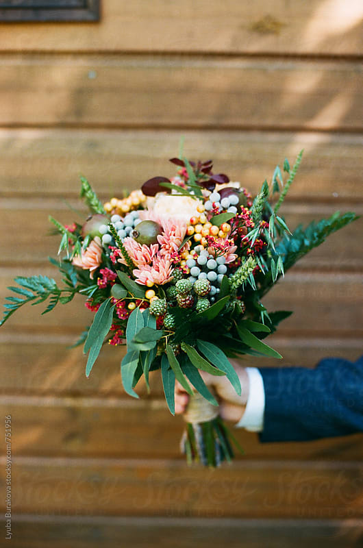 Man holding a wedding bouquet by Lyuba Burakova for Stocksy United