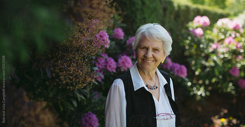 Portrait of happy senior woman outside in garden by Rob and Julia Campbell for Stocksy United