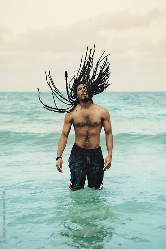 A Man Flips his Dreadlocks at the Beach by Stephen Morris for Stocksy United