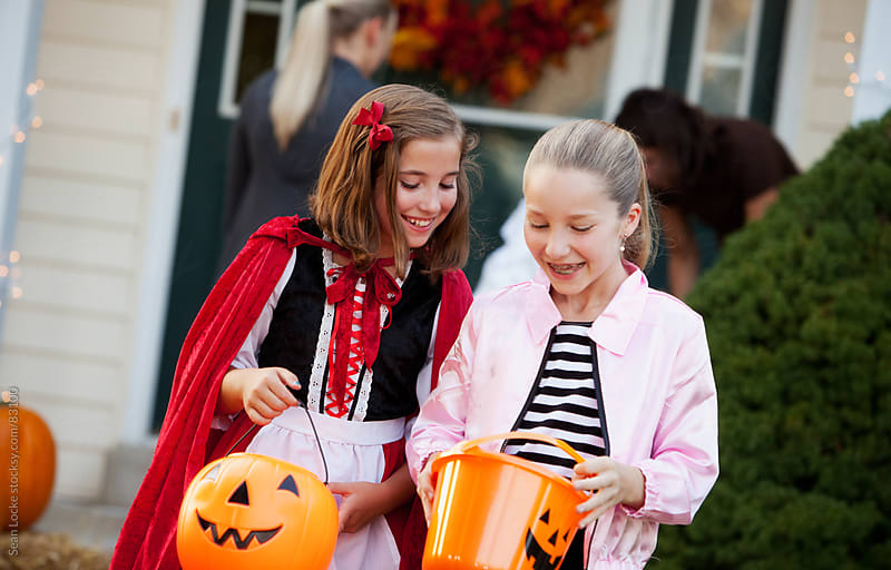 Halloween: Friends Look At Trick-Or-Treat Candy In Bucket by Sean Locke for Stocksy United