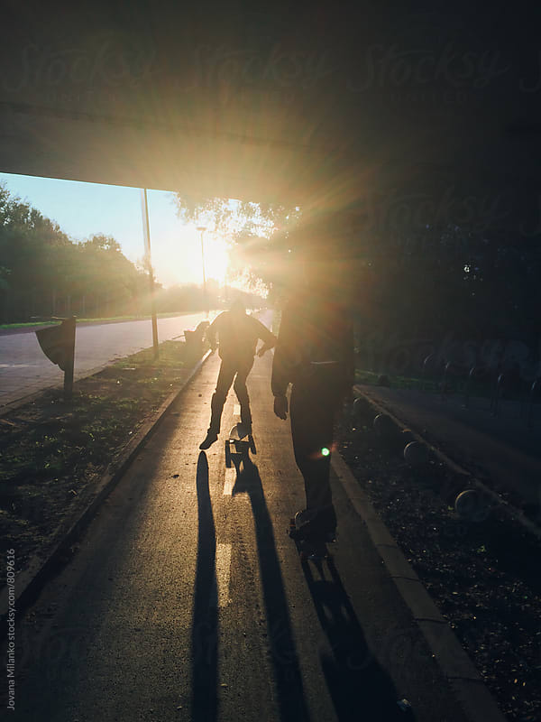 Two young guys riding  longboards in the city at sunset by Jovana Milanko for Stocksy United