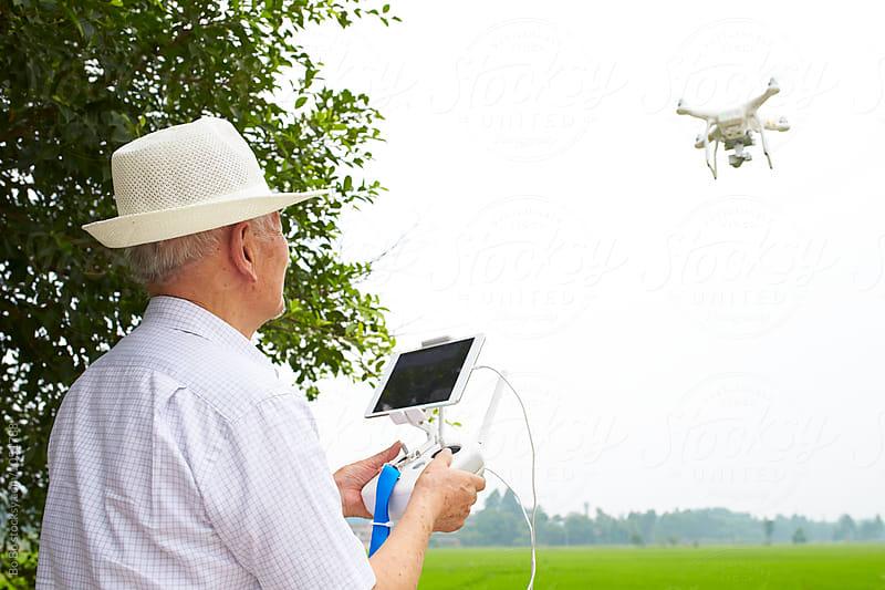 Senior asian man flying drone by Bo Bo for Stocksy United
