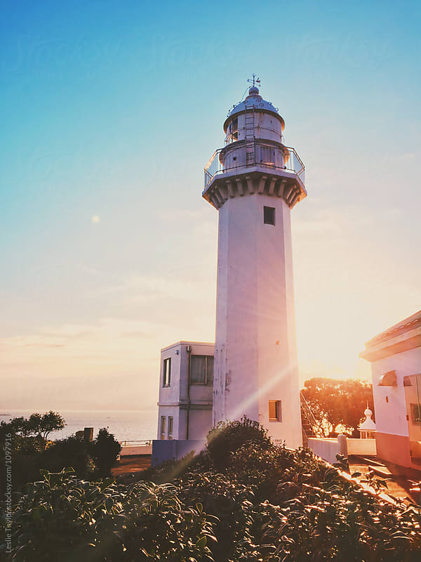 The Sun Rises Behind A Lighthouse by Leslie Taylor for Stocksy United