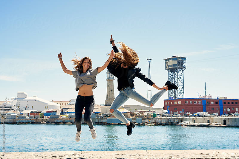 Two young friends jumping in poses at waterfront by Guille Faingold for Stocksy United
