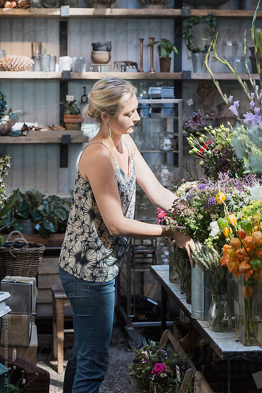Young attractive woman arranging vases in flower shop by Lior + Lone for Stocksy United