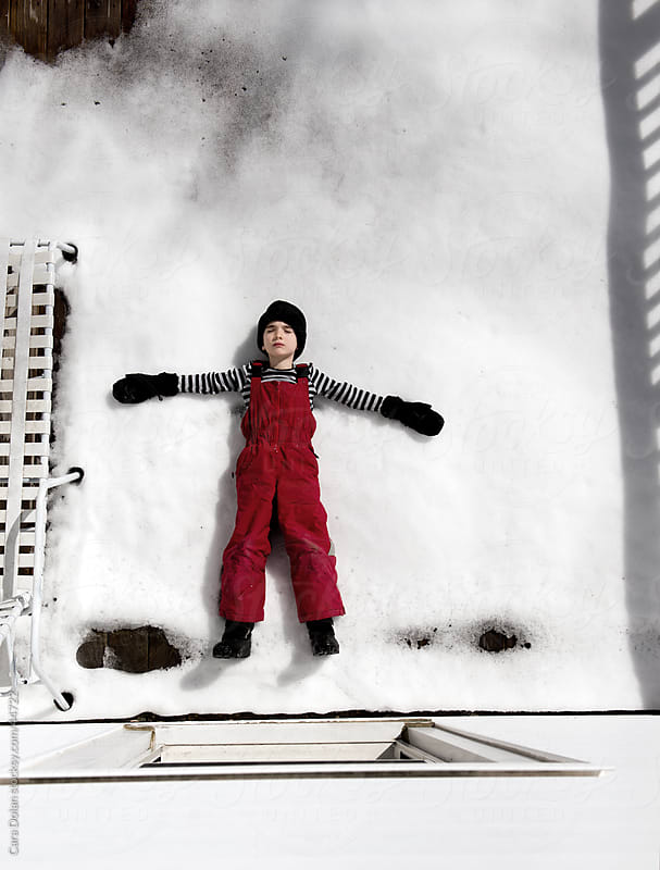 Boy in winter gear lies on snow covered deck with his eyes closed  by Cara Slifka for Stocksy United