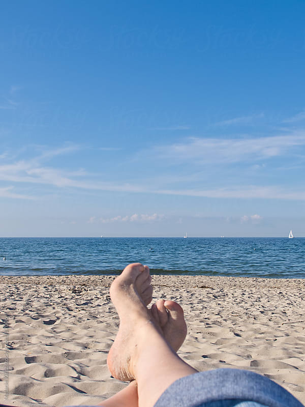 A person relaxing at the beach on a sunny day by Melanie Kintz for Stocksy United