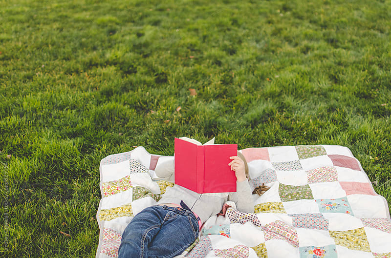 Child reading on a picnic blanket by Lindsay Crandall for Stocksy United