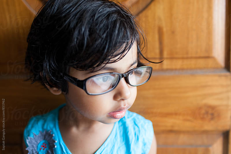 Portrait of a cute little girl with glasses looking seriously by Saptak Ganguly for Stocksy United