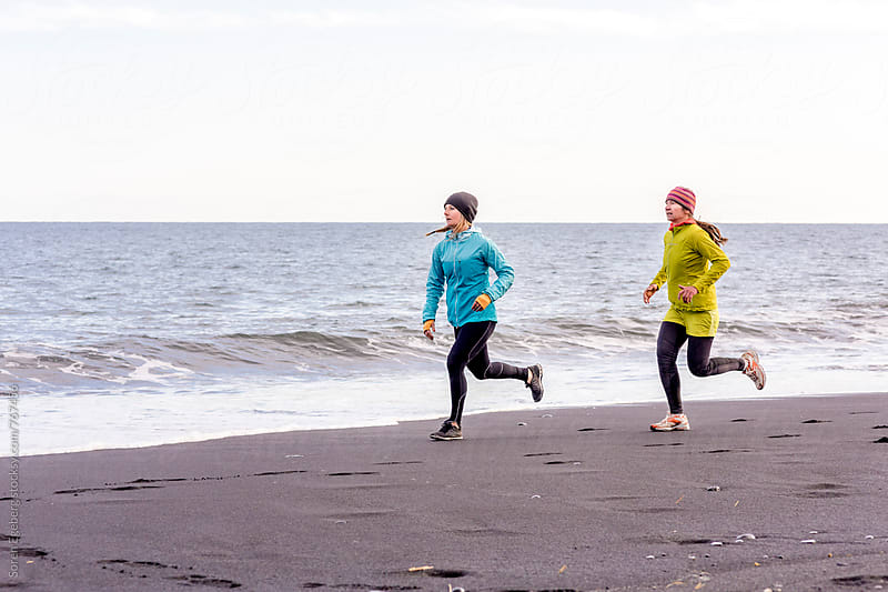 Two female runners running on black beach in Iceland by Søren Egeberg Photography for Stocksy United