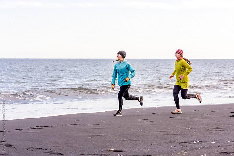 Two female runners running on black beach in Iceland by Soren Egeberg for Stocksy United