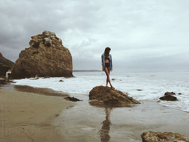Woman Standing on Sea Shore Rock by Kevin Russ for Stocksy United