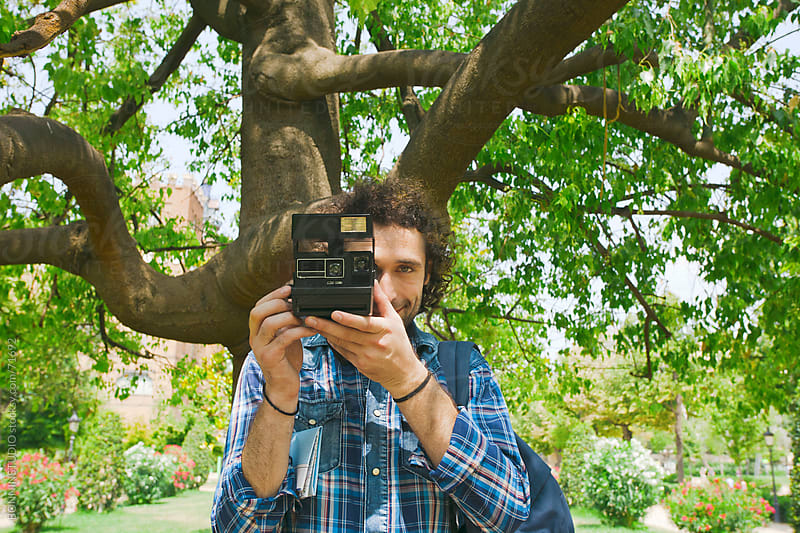 Young man taking photos with instant camera under a big tree. by BONNINSTUDIO for Stocksy United
