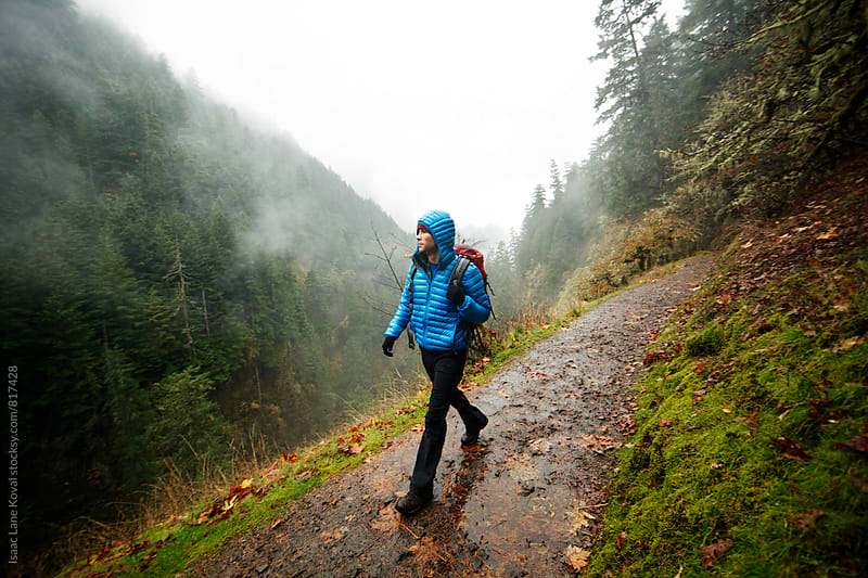 Man hiking on cliff side trail with rain coming down by Isaac Lane Koval for Stocksy United
