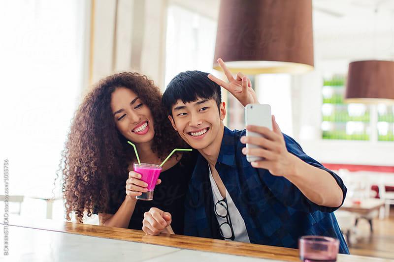 Trendy couple taking selfie having breakfast in a coffee shop. by BONNINSTUDIO for Stocksy United